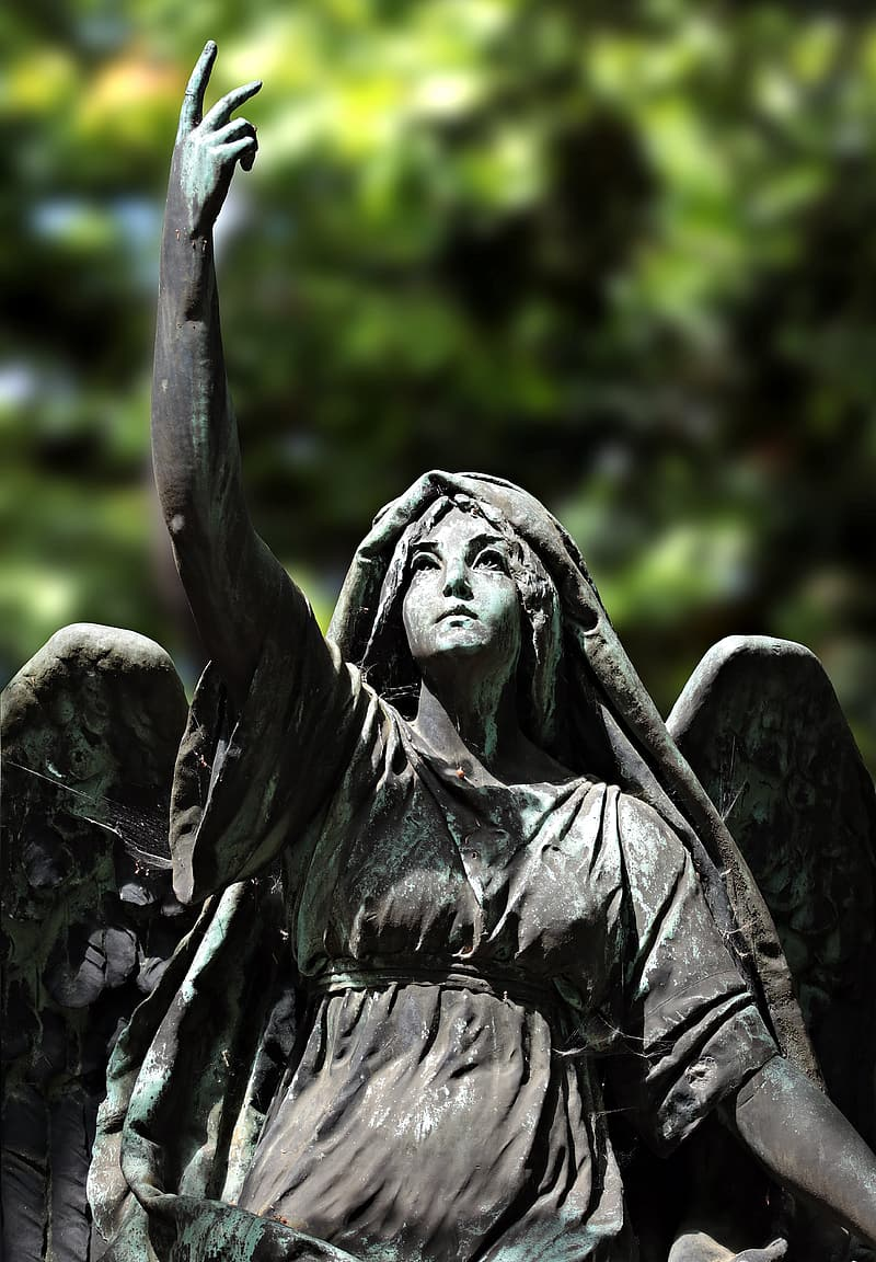 Selective focus photography of gray angle statuette