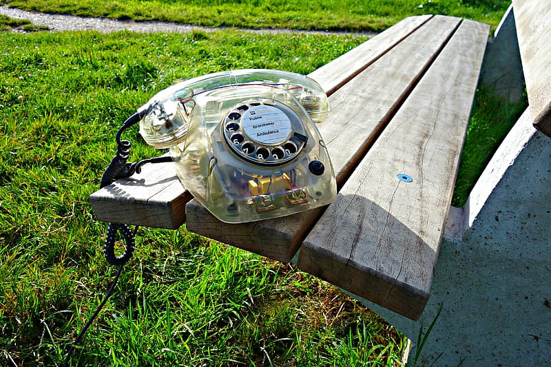 Clear rotary phone on wooden bench during daytime