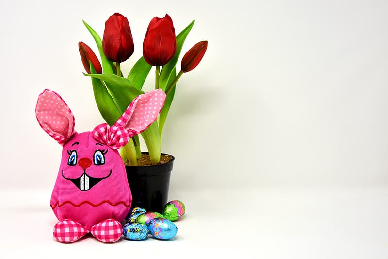 Red and pink heart ceramic figurine beside red tulips