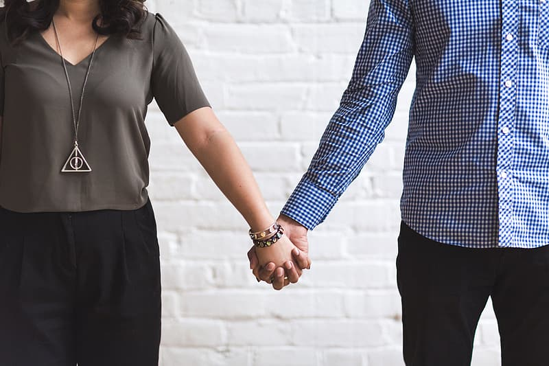 Woman holding hands with man while standing beside wall