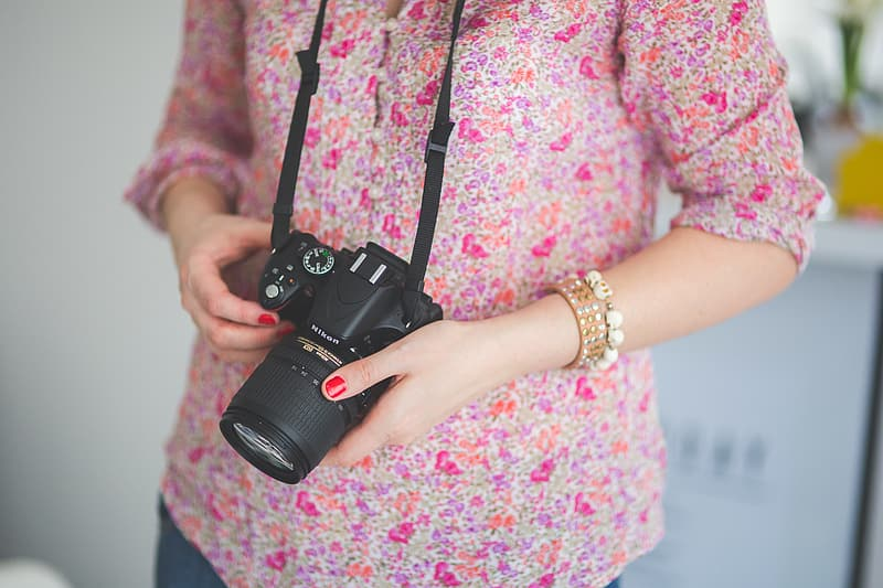 Person wearing red floral shirt holding black DSLR camera