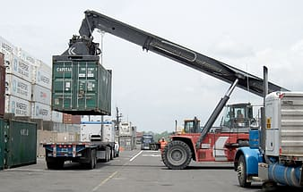 Red and black heavy equipment carrying green intermodal container