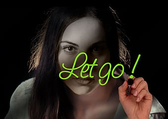 Woman wearing white shirt with let go! text overlay
