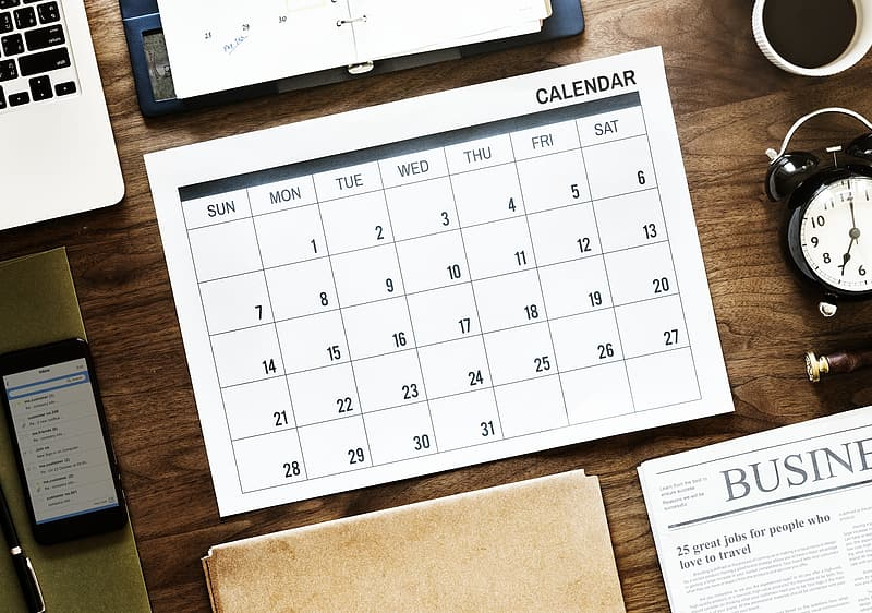 White and black calendar on brown wooden table