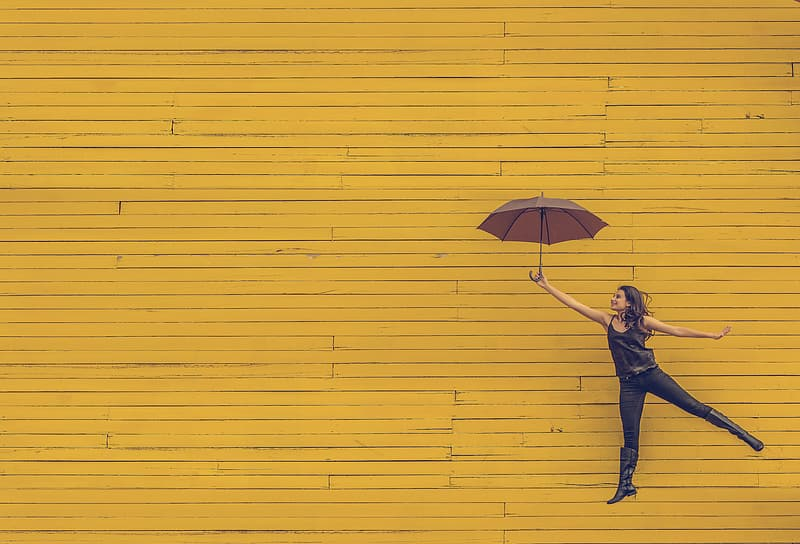 Woman holding umbrella with yellow background