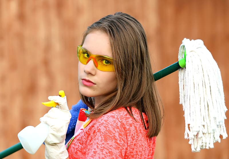 Woman holding mop and spray bottle