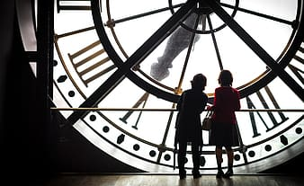 Silhouette view of two women standing in front of big clock
