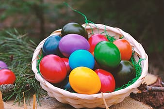 Red blue and yellow egg on brown woven basket