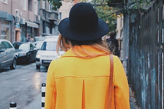 Woman in yellow coat with black hat