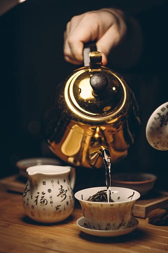 Person holding brass kettle under white teacup on white saucer