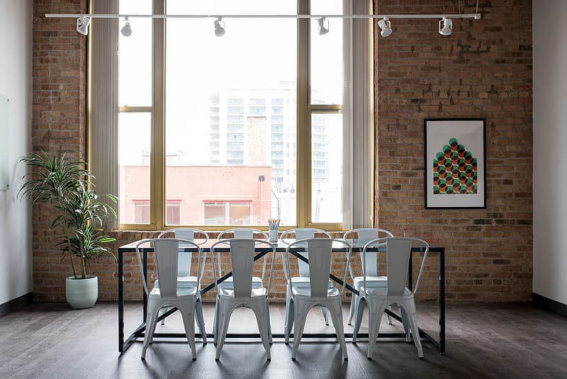 Rectangular black metal-framed glass-top table with chairs near window