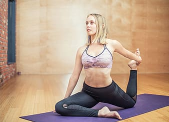 Woman in white sports bra and black leggings sitting on black yoga mat