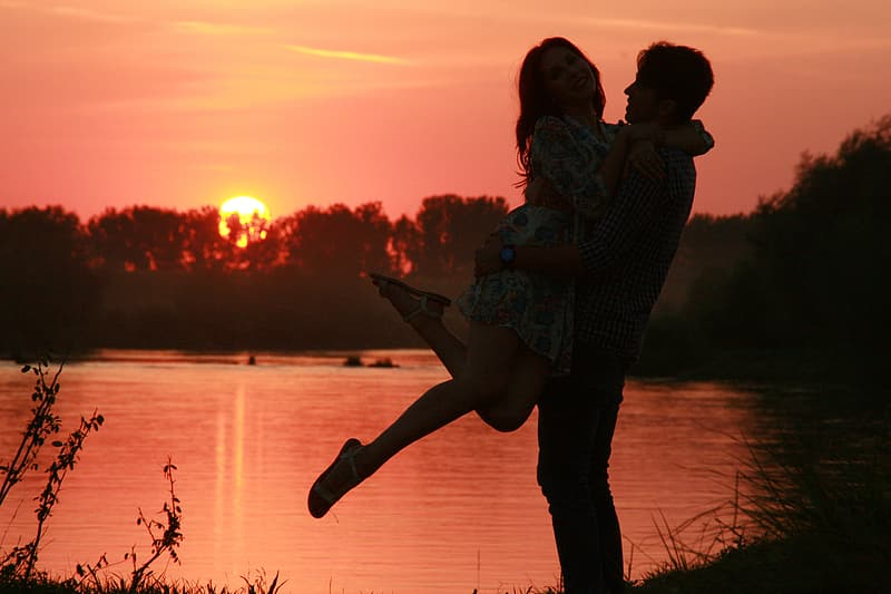 Silhouette of man carrying a girl in front of water pond during sunset