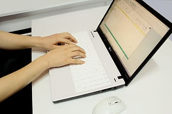 Person using white laptop computer