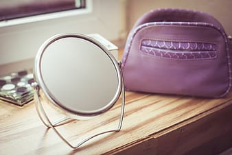 Round mirror with silver frame on brown wooden table