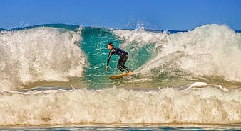 Man in black wetsuit surfing on sea waves during daytime