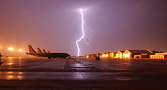 Airplane parked on concrete road with lightning thunder during nighttime