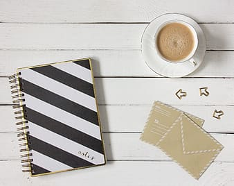 White and black striped notebook and white ceramic tea cup and saucer set