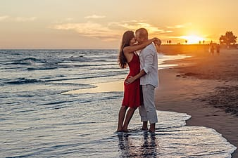 Man and woman standing on seashore during daytime