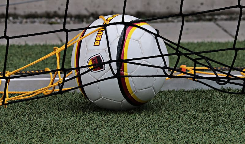 White, yellow, and black soccer ball on green grass