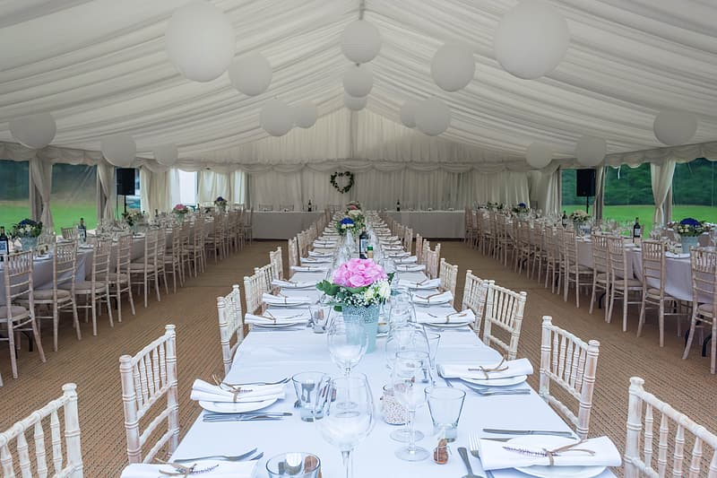 Photography of tables and chairs under marquee