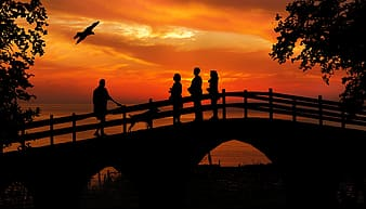 Silhouette of people standing on bridge during sunset