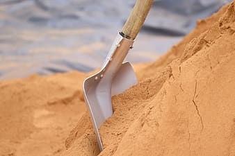 Brown and white shovel on brown rock