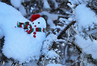 Red and white snowman with red scarf on snow covered ground