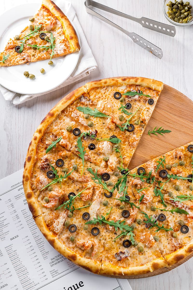 Pizza with black olives on brown tray