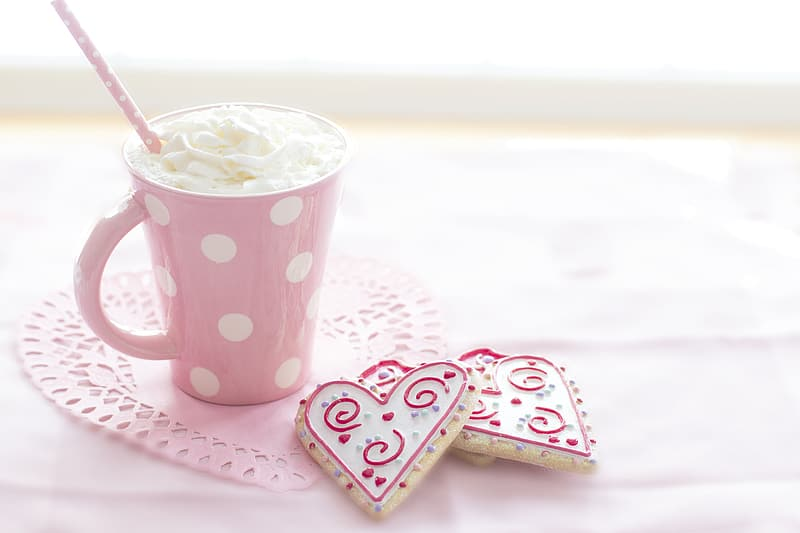 White ceramic mug filed with cream beside two heart-shaped cookies