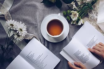 Person placing book beside cup and saucer