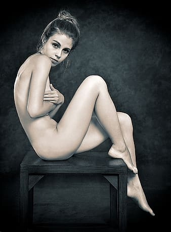 Nude woman sitting on brown wooden table