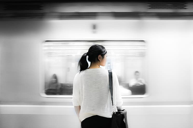 Woman in white shirt and black skirt standing in train station