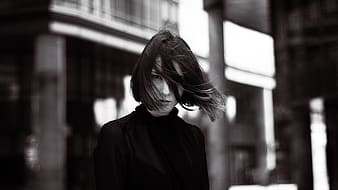 Gray scale photo of woman wearing turtle-neck shirt on building background