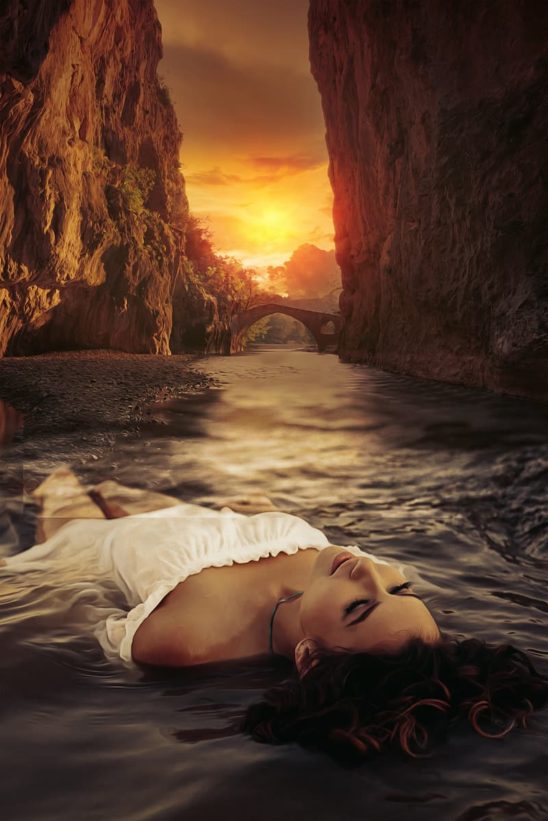Woman in white dress lying on body of water