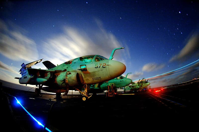 Green and white jet plane under blue sky during night time