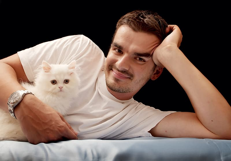 Man in white crew neck t-shirt smiling and holding white cat