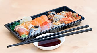 Served raw meat on rectangular plastic tray with chopsticks on top of filled white ceramic saucer