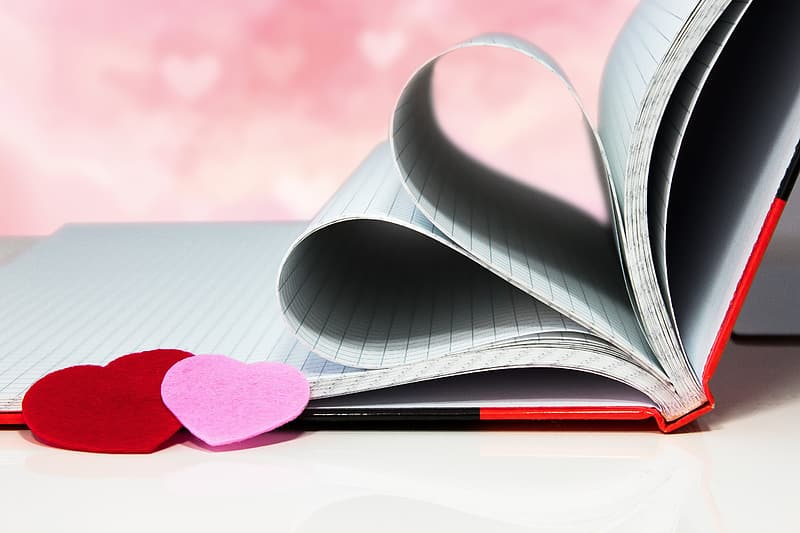 Red heart on white book page