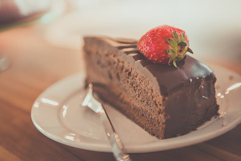 Sliced chocolate cake with strawberry topping in white ceramic saucer with stainless steel fork