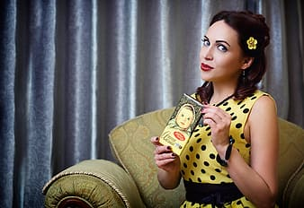 Woman in yellow and black polka-dot sleeveless top sitting on sofa chair