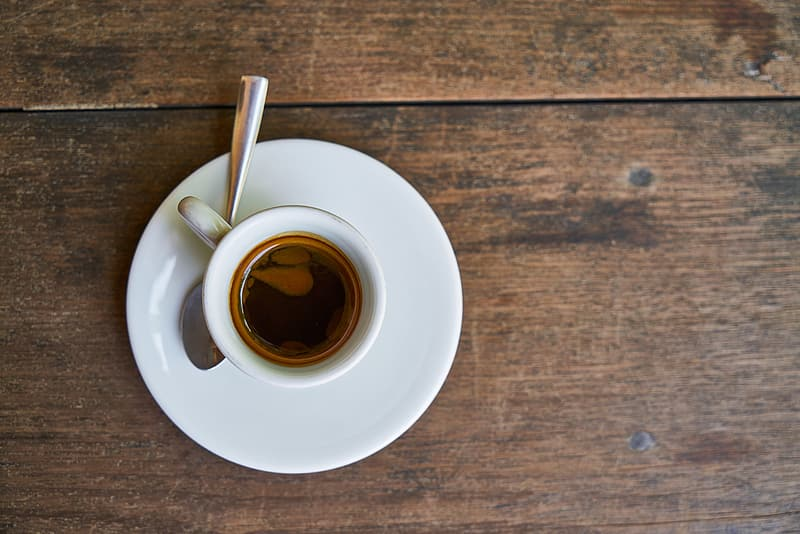 White ceramic coffee cup on brown wooden table