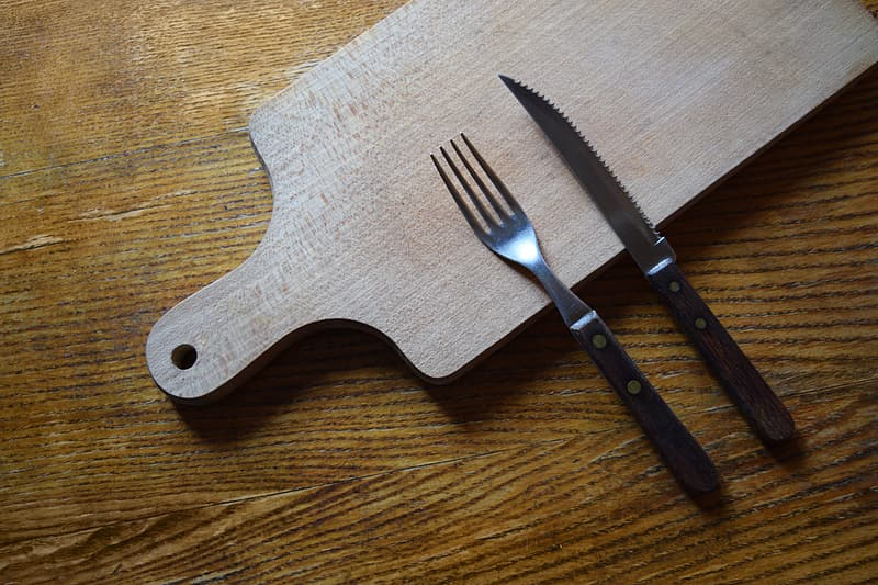 Stainless steel fork beside knife on top of wooden chopping board