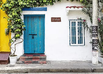Blue wooden door on white concrete house