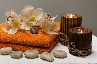 White orchids and two brown candles on top of orange towel closeup photography