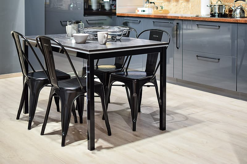 Black dining table with 4 chairs near blue cabinetry