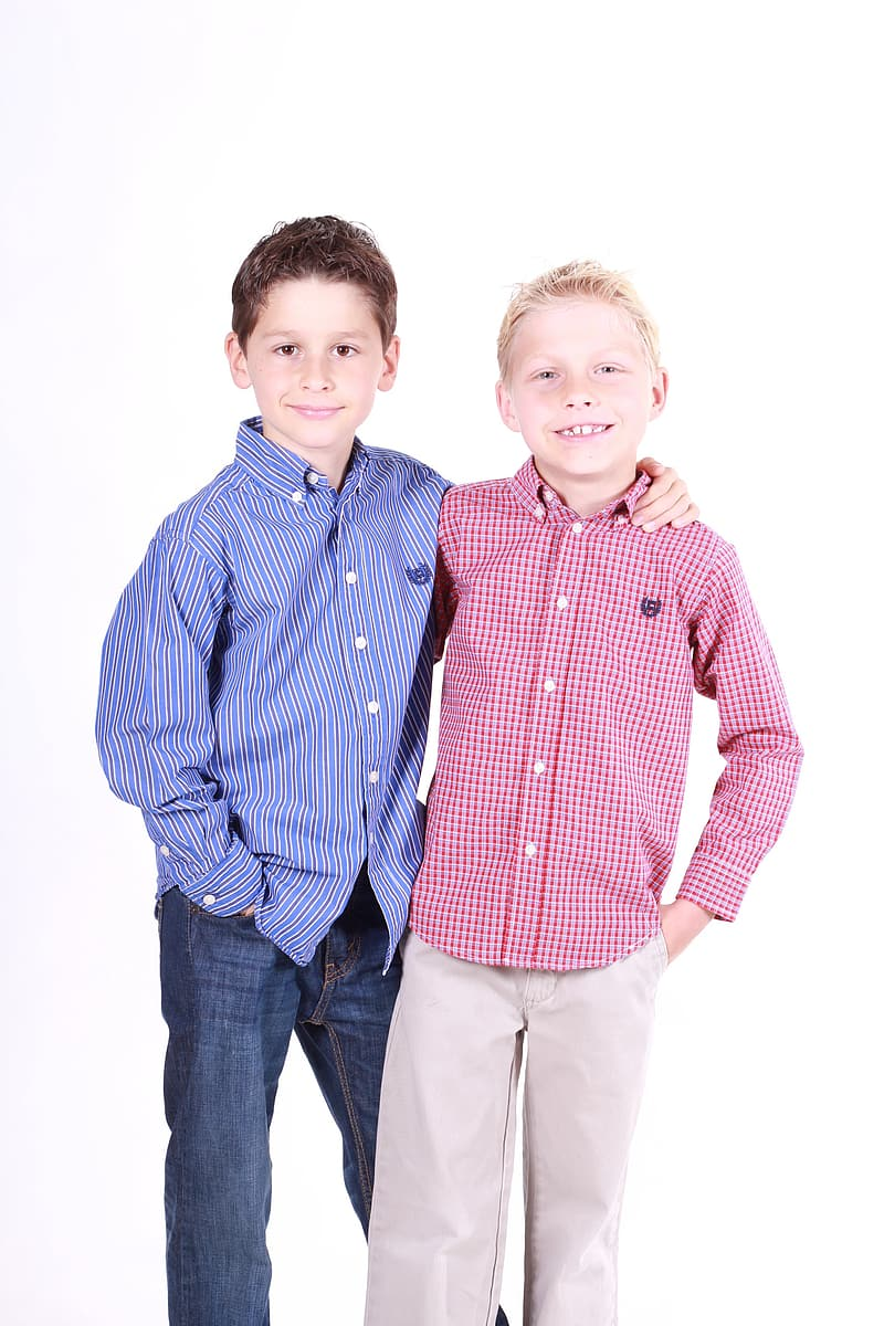 Two boys in red and blue button-up sport shirts and denim pants