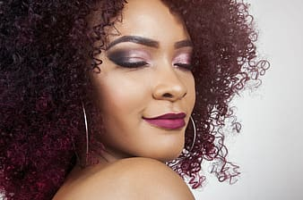 Woman with burgundy curly hair wearing smokey pink tone eyeshadow, matte lipstick, and silver-colored hoop earrings