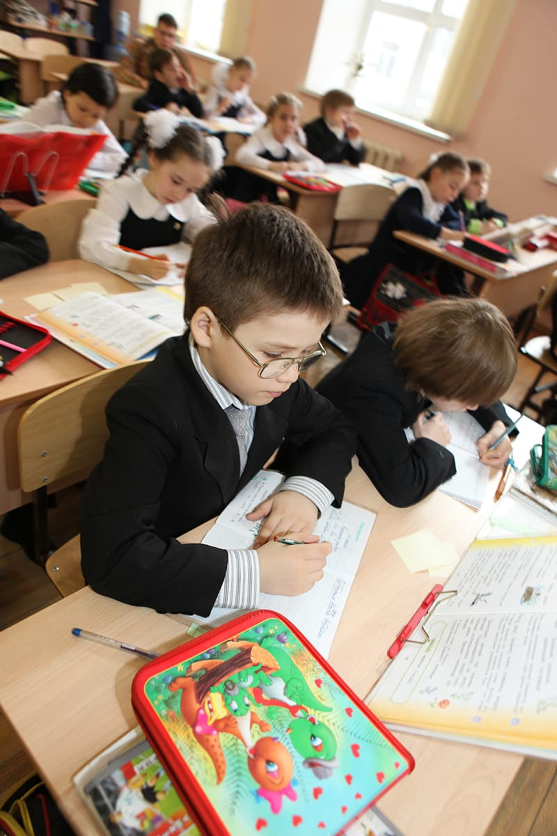 Boy in black suit jacket writing on white paper