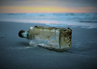 Clear glass bottle on gray sand during sunset